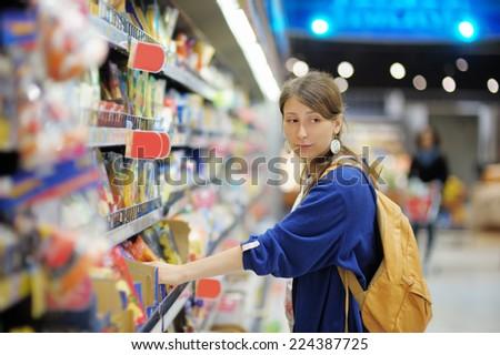 Beautiful young woman buying food at supermarket  - stock photo