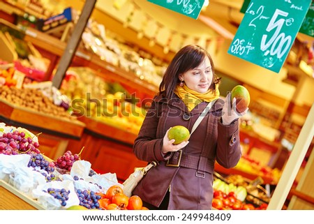 Beautiful young woman buying fresh fruits at market - stock photo