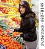 Beautiful young woman buying fruits and vegetables at a produce department of a supermarket/grocery store - stock photo