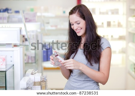 Beautiful young woman buying perfume. Selective focus.