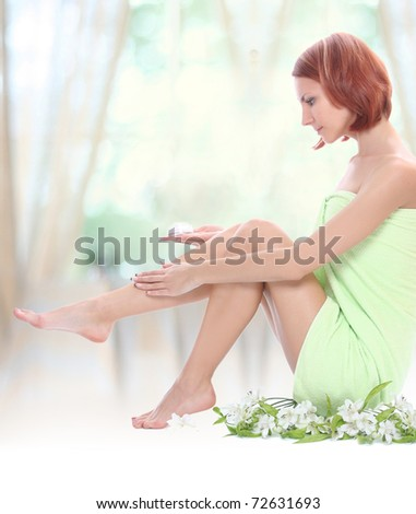 beautiful young woman caring for her legs - stock photo