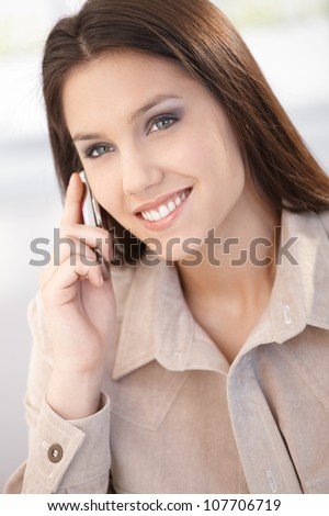 Beautiful young woman chatting on mobile phone, smiling.