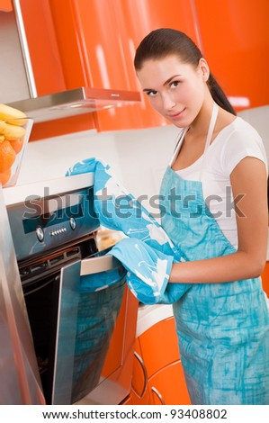 Beautiful young woman checking how her cookies is doing in the oven