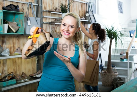 Beautiful young woman choosing a pair of shoes while other customer still  looking - stock photo