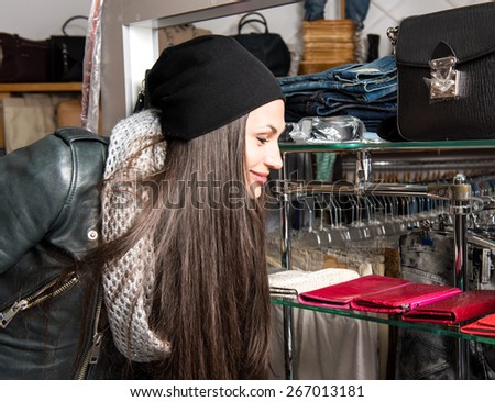 Beautiful young woman choosing leather purse in the mall - stock photo