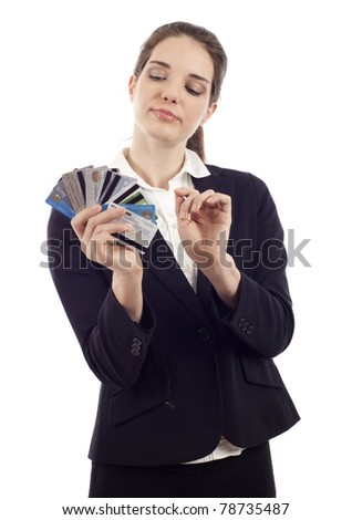 Beautiful young woman choosing which credit card to pay with, isolated over white - stock photo