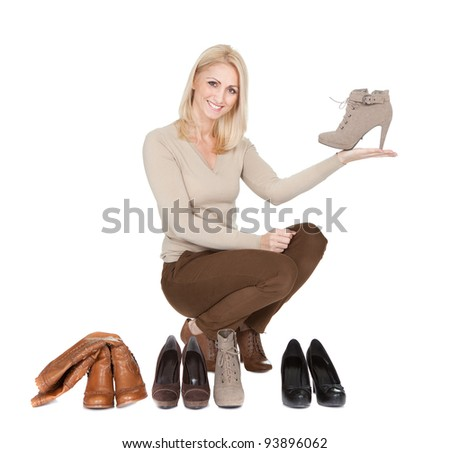 Beautiful young woman chosing shoes to wear. Isolated on white - stock photo