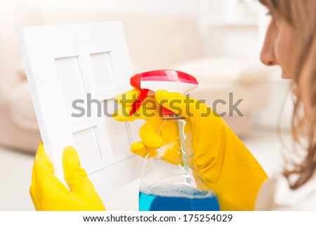 Beautiful young woman cleaning frame in her home wearing yellow gloves and using cleaning spray - stock photo