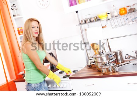 Beautiful young woman cleans the oven in the kitchen, wearing yellow gloves - stock photo