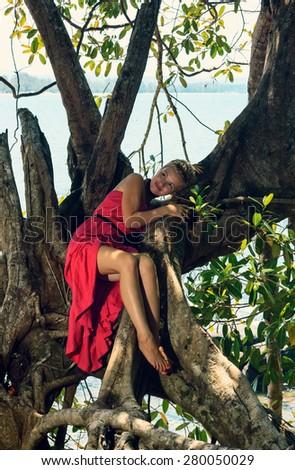 Beautiful young woman climbing a big exotic tree at seashore in long red dress and enjoying beautiful tropical nature view 3 - stock photo