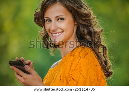 Beautiful young woman close-up in orange sweater is typing with stylus on device, against green of summer park. - stock photo