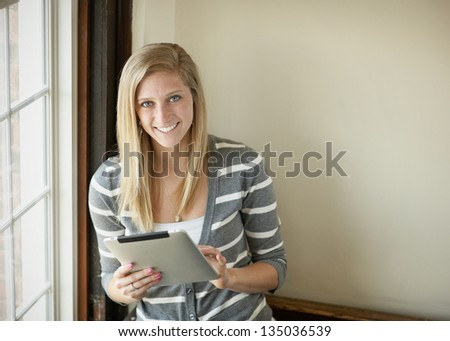 Beautiful young woman college student with tablet computer - stock photo