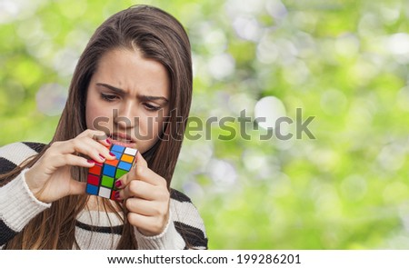 beautiful young woman concentrated solving the Rubik's Cube - stock photo