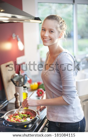 beautiful young woman cooking at home - stock photo