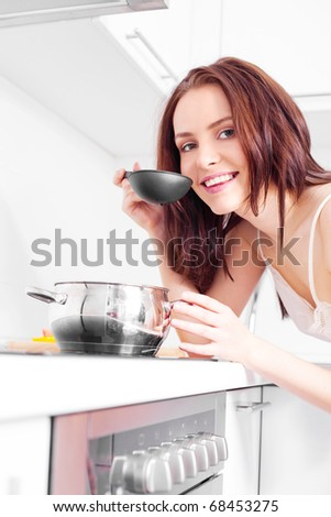 beautiful young woman cooking dinner in the kitchen