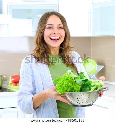 Beautiful Young Woman cooking fresh Vegetables.Dieting Concept.Vegetarian food - stock photo