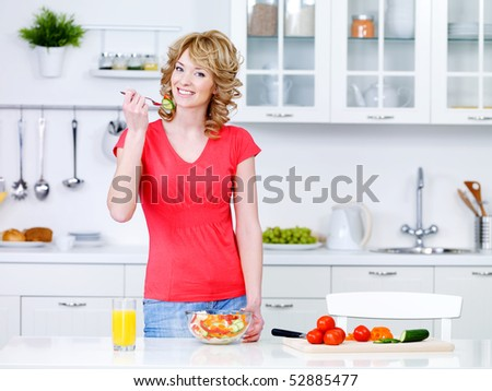 Beautiful young woman cooking healthy food and eating salad in the kitchen - stock photo
