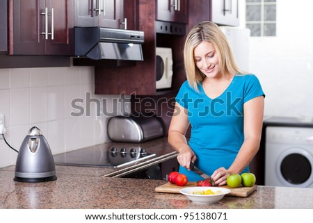 beautiful young woman cooking in modern kitchen - stock photo