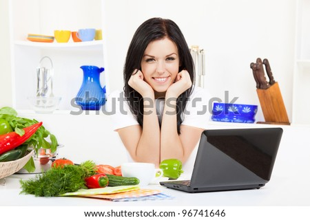 Beautiful young woman cooking looking at camera happy smile, laptop with receipt in the kitchen - stock photo