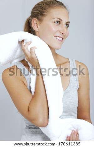 Beautiful young woman cooling off after exercising with a towel.