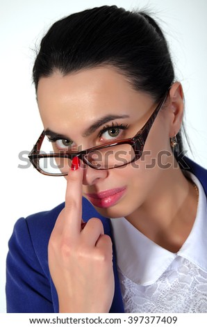 Beautiful, young woman corrects glasses middle finger. - stock photo