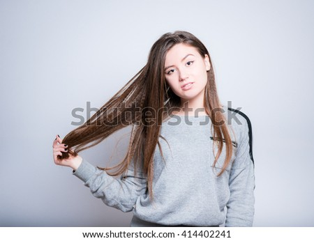 beautiful young woman corrects long hair, close-up isolated on white background - stock photo