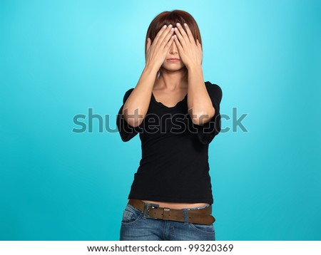 beautiful, young woman covering her eyes with her hands, on blue background - stock photo