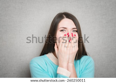 Beautiful young woman covering the face with her hand - stock photo
