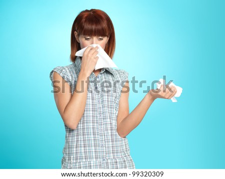beautiful young woman, crying, blowing her nose, on blue background