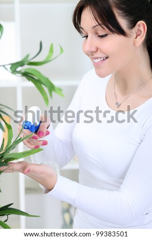 beautiful young woman cultivating flowers in domestic room - stock photo