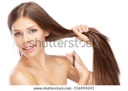 Beautiful young woman cutting her hair, white background - stock photo