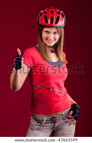 beautiful young woman cyclist in a red shirt and a helmet shows thumb - stock photo