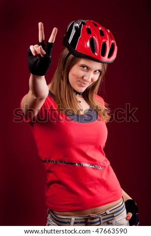 beautiful young woman cyclist in a red shirt and a helmet  with victory fingers - stock photo