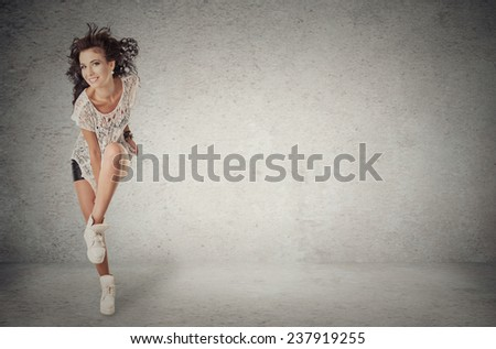 Beautiful young woman dancer is standing showing hip hop move pose. Full length studio shot isolated on grey wall background. Positive face expression, emotion, body language. Fashion trendy teenager - stock photo