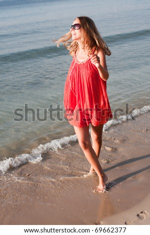 beautiful young woman dancing on the beach - stock photo