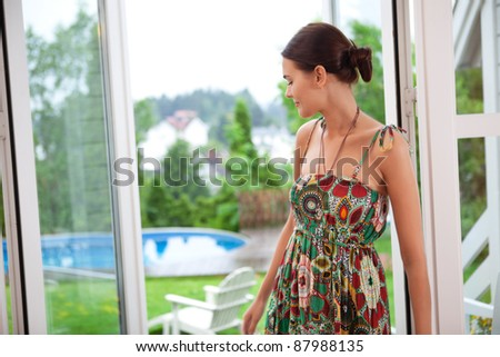 Beautiful young woman daydreaming while standing near door - stock photo