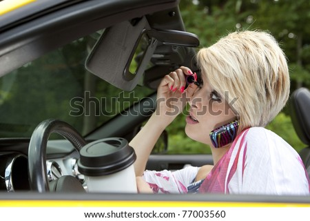 Beautiful young woman distracted while driving - stock photo
