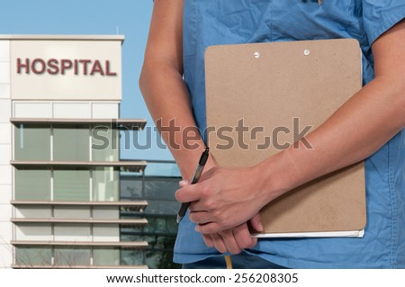 Beautiful young woman doctor in scrubs holding a patient record - stock photo