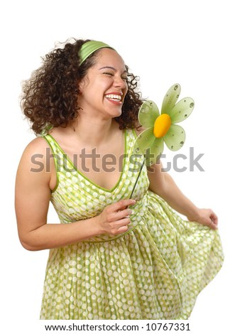 Beautiful young woman doing a playful curtsy while holding a spring flower - stock photo