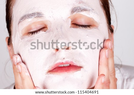 Beautiful young woman doing cosmetic mask on her face