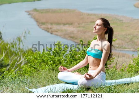 Beautiful young woman doing exercise outdoors on summer day - stock photo