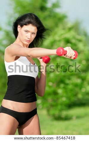 Beautiful young woman doing exercise with dumbbell in green park. Summer - stock photo