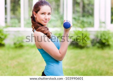 Beautiful young woman doing exercises with dumbbell outdoor - stock photo