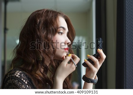 Beautiful young woman doing her makeup looking in the mirror . - stock photo