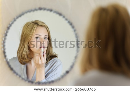 Beautiful young woman doing make-up  - stock photo