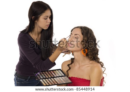 Beautiful young woman doing makeup on a white background closeup
