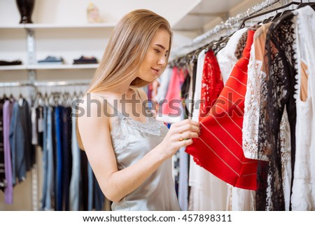 Beautiful young woman doing shopping and choosing clothes in shop - stock photo