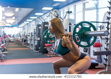 Beautiful young woman doing squats with barbell - stock photo