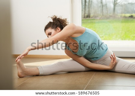 Beautiful young woman doing stretching exercise indoor in front of the window. Yoga  - stock photo