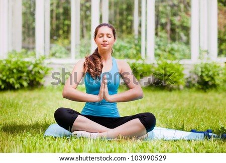 Beautiful young woman doing stretching exercise on green grass at park. - stock photo